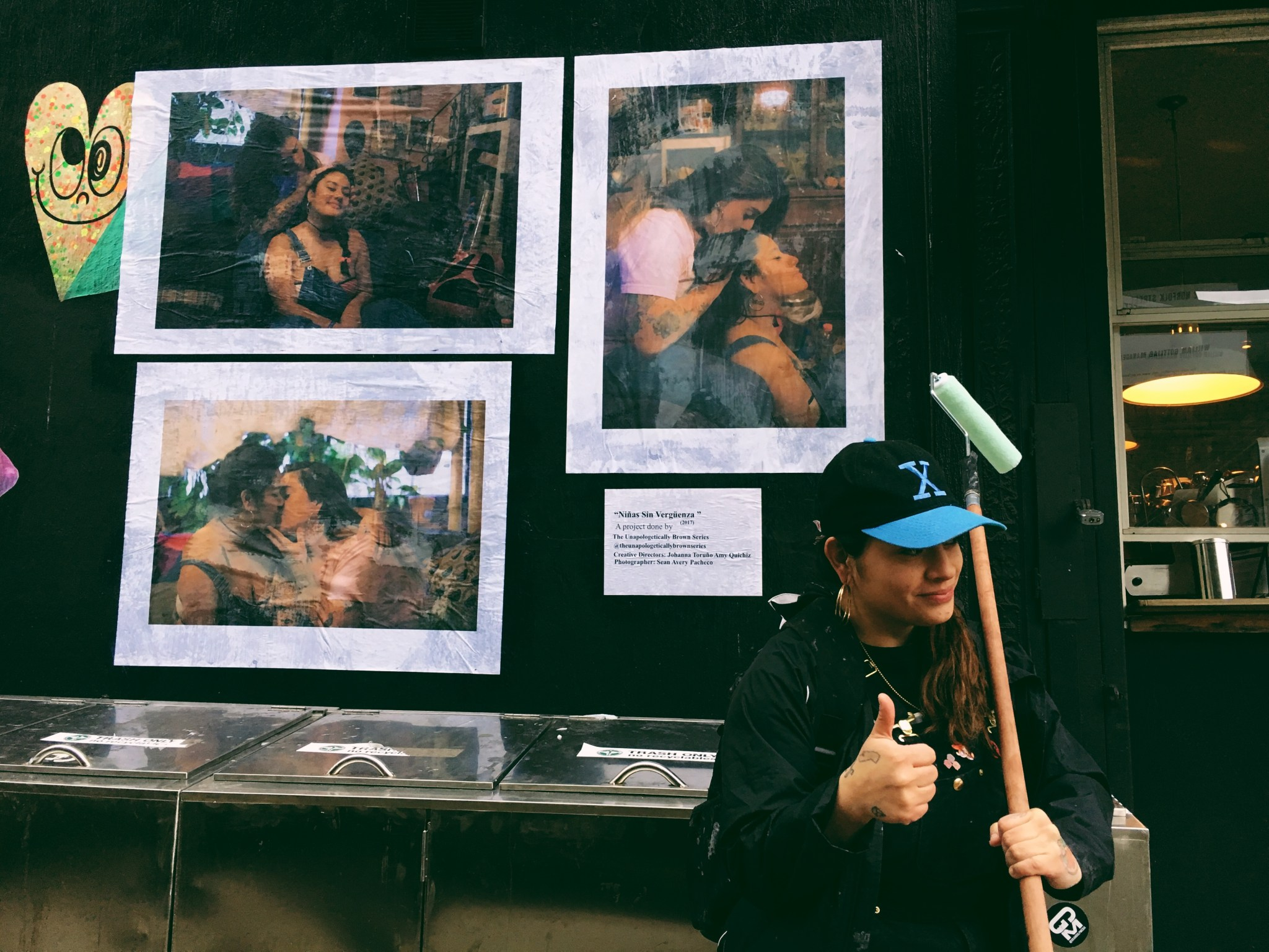 """A medium-skinned woman wearing a black baseball cap with a blue """"X"""" on it stands in front of several photographs wheatpasted to a dark wall. She give the camera a thumbs up."""