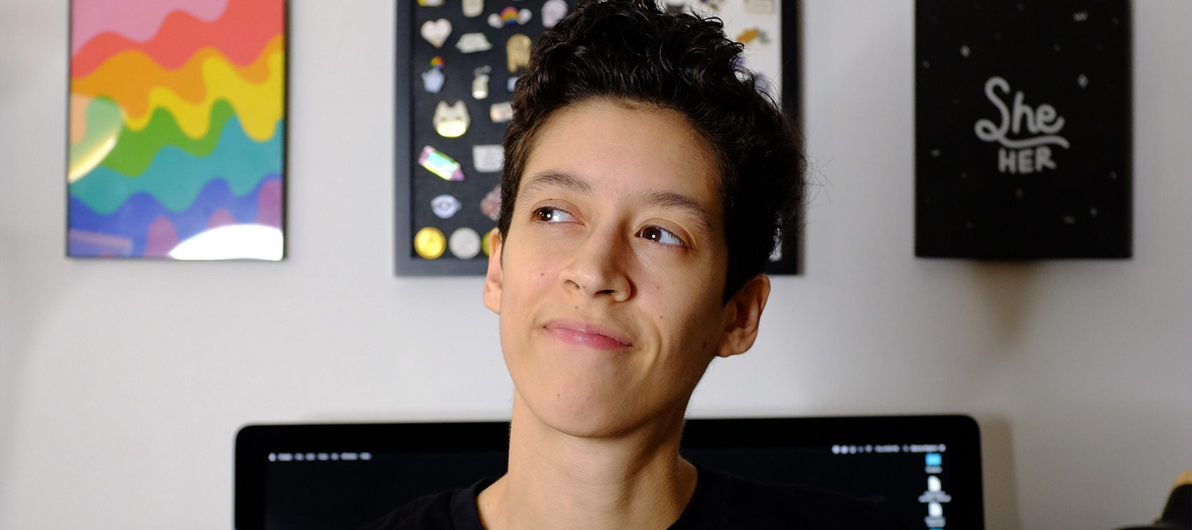 A medium-skinned woman with her short, black hair worn in a pixie cut wears a black shirt with the phrase