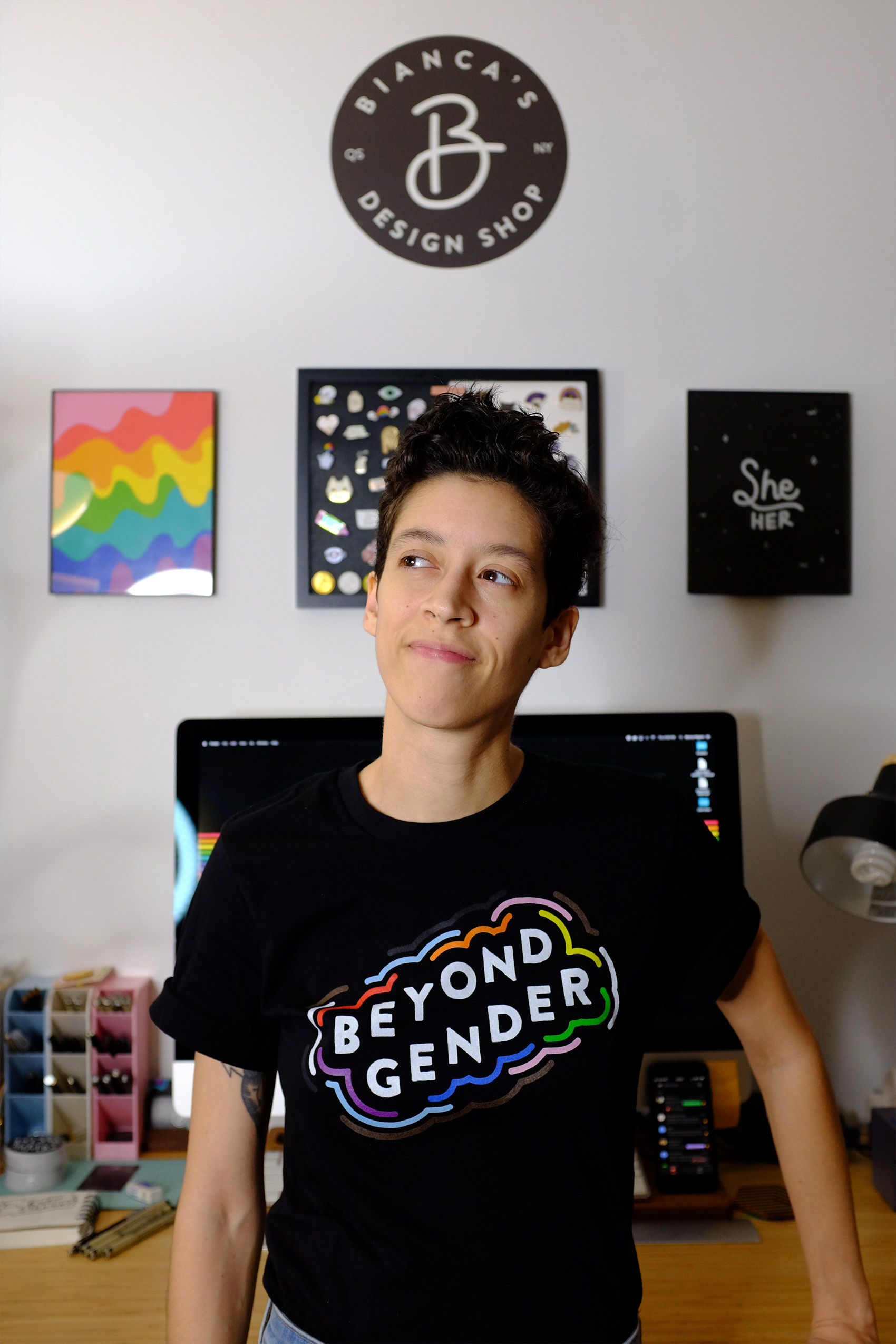 """A medium-skinned woman with her short, black hair worn in a pixie cut wears a black shirt with the phrase """"Beyond Gender"""" written on the front surrounded by colorful squiggles. Behind her is a large Mac computer and a few graphic prints hung on the wall."""