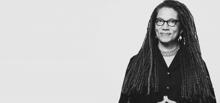 A black-and-white photo of an light-skinned African American woman with long dreadlocks. She wears a button-up black shirt and black-rimmed glasses. She stands with her hands clasped in front of her and smiles warmly at the camera.