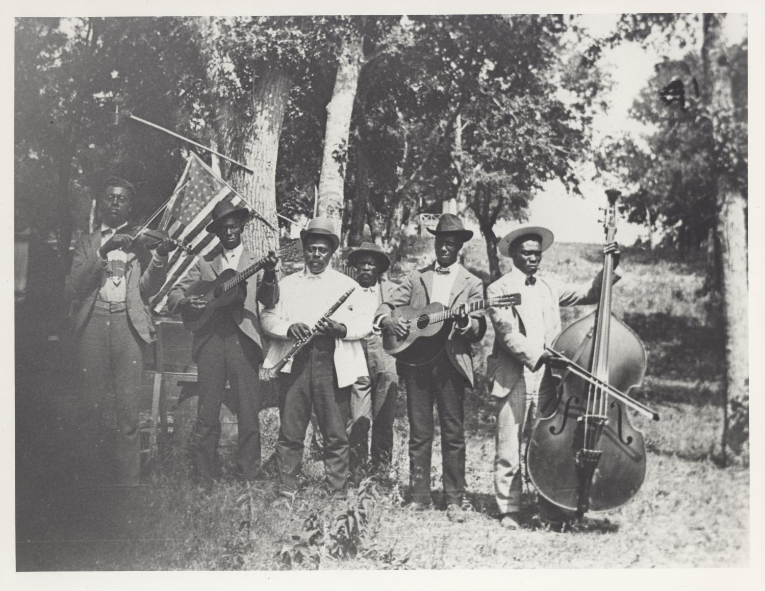 A vintage, black-and-white photo of a group of dark-skinned African American men standing in a wooded area. They are dressed in top hats, suit jackets, and slacks. Most all hold an instrument, including guitars, a cello, violin, and flute. Behind them an American flag is hanging off of a tree.