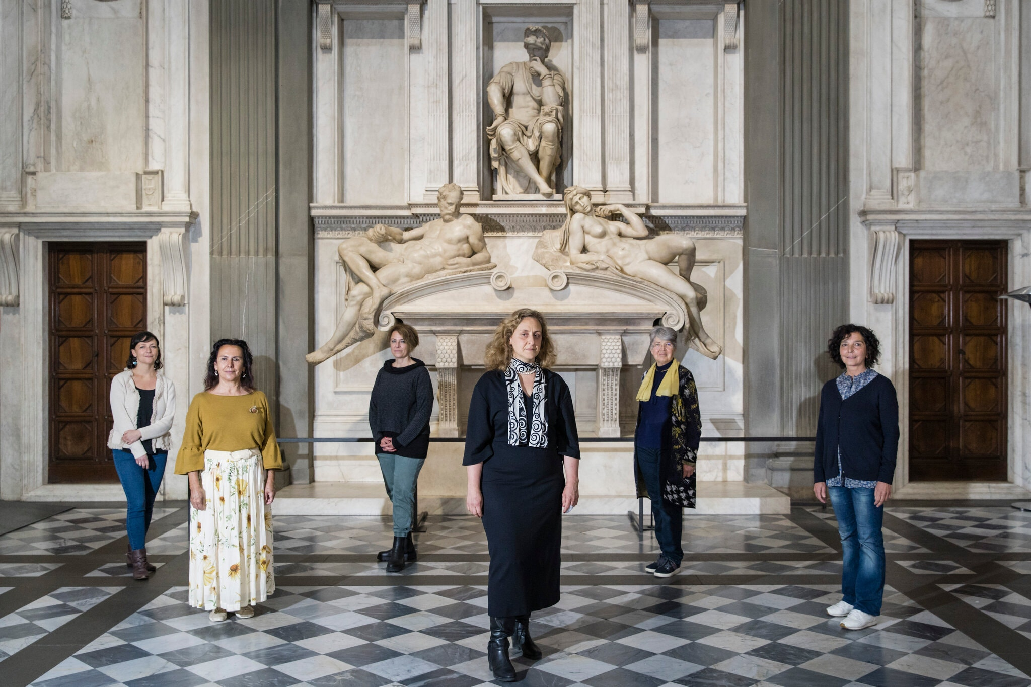 In an ornate, marble hall, with columns and carved statues against the far back wall, six light-skinned woman stand spaced out from one another in a zig/zag pattern. Some wear jeans an sneakers, other are in dresses with boots. They all stare directly at the camera.