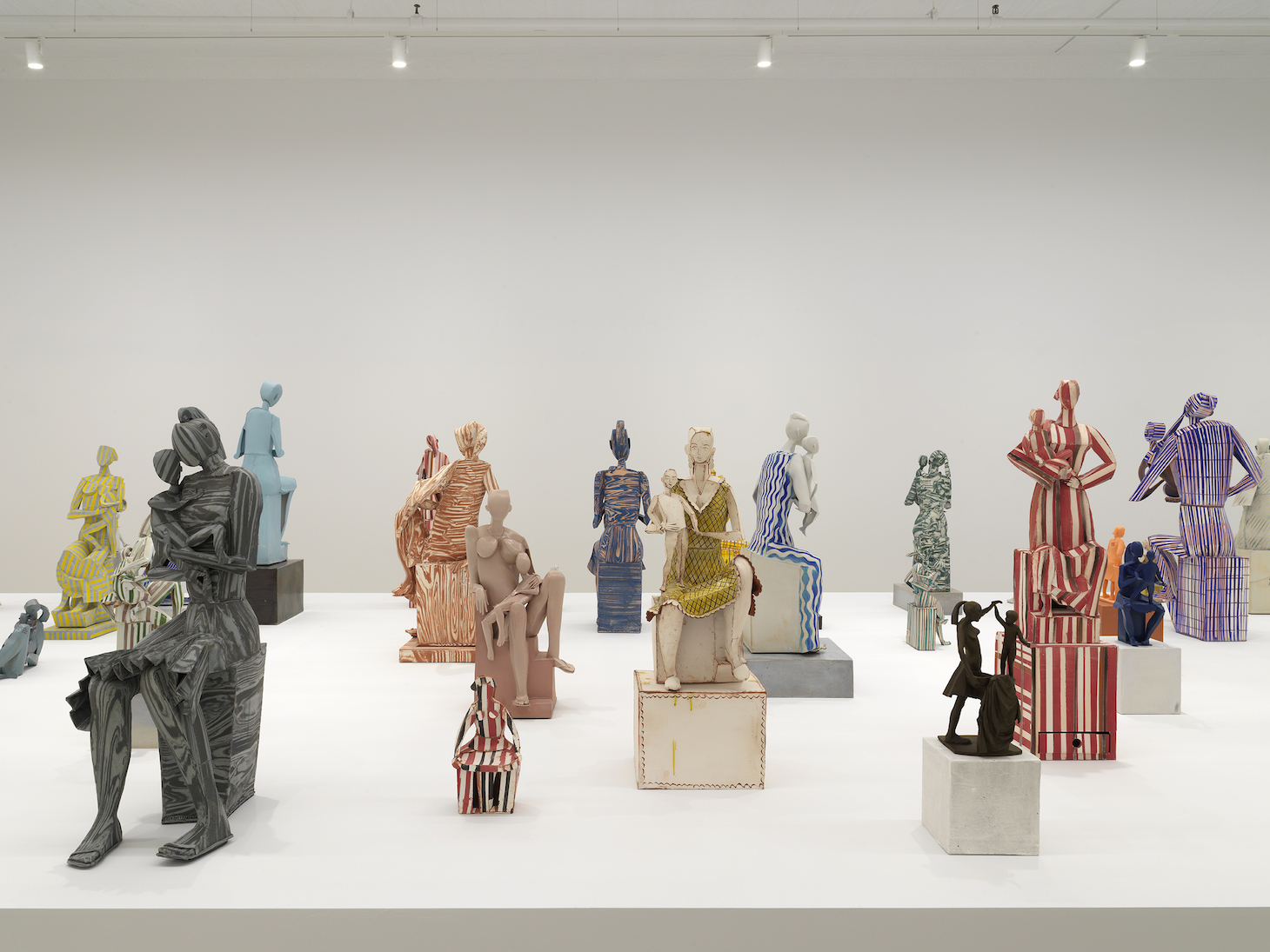 A photograph of approximately twenty abstract Madonna statues on a white table in a sparse gallery. Most are accompanied by a female infant or child. Their bodies are schematic and cubistic. Some figures are nude, some are clothed, some are monochromatic, and some are striped. The statues are all of varying sizes, ranging from under eight inches to three-feet tall.