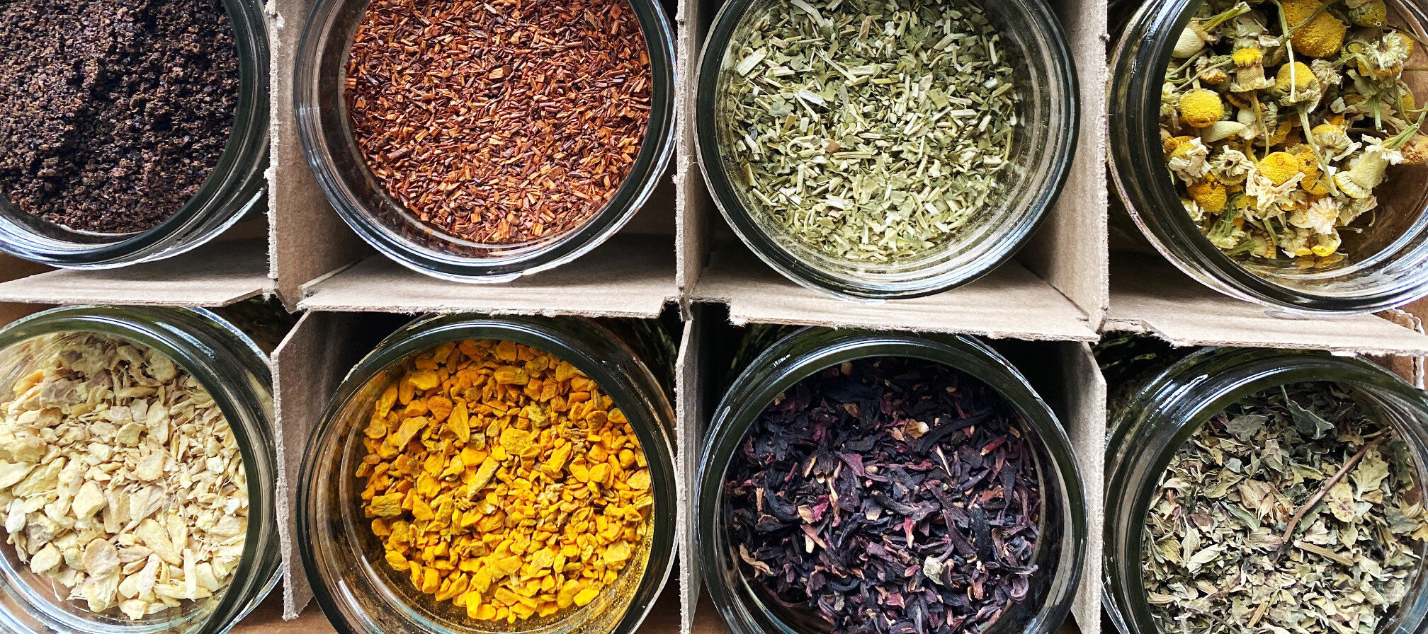 An arial view of round jars full of colorful spices, arranged in a four by three cardboard grid.