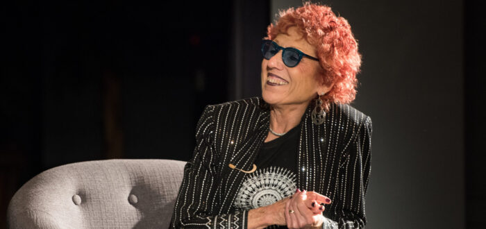 A light-skinned woman with red, cropped hair sits on a plush grey chair on a stage. She looks to the left smiling, with her hands clasped. She wears a