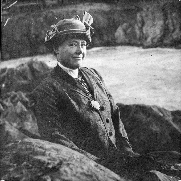 A black-and-white photo of a light-skinned woman from the early 1900s posing between large rocks with a river behind her. She wears formal dress and a hat and smiles slightly at the camera.