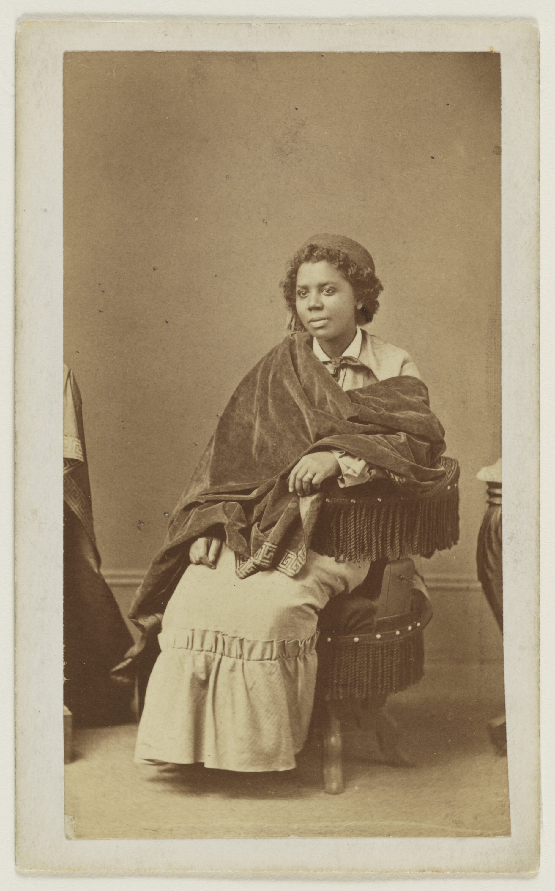 A black and white photograph from the late 1800s of a dark skinned woman seated on an upholstered chair with fringe around the arm and seat. She is wearing a white collared shirt with a scarf tied around her neck, a light colored jacket and a matching ankle length skirt. There is heavy, dark colored velvet fabric draped from her right shoulder to her left arm. She is wearing a round, flat-topped hat over her short wavy hair.