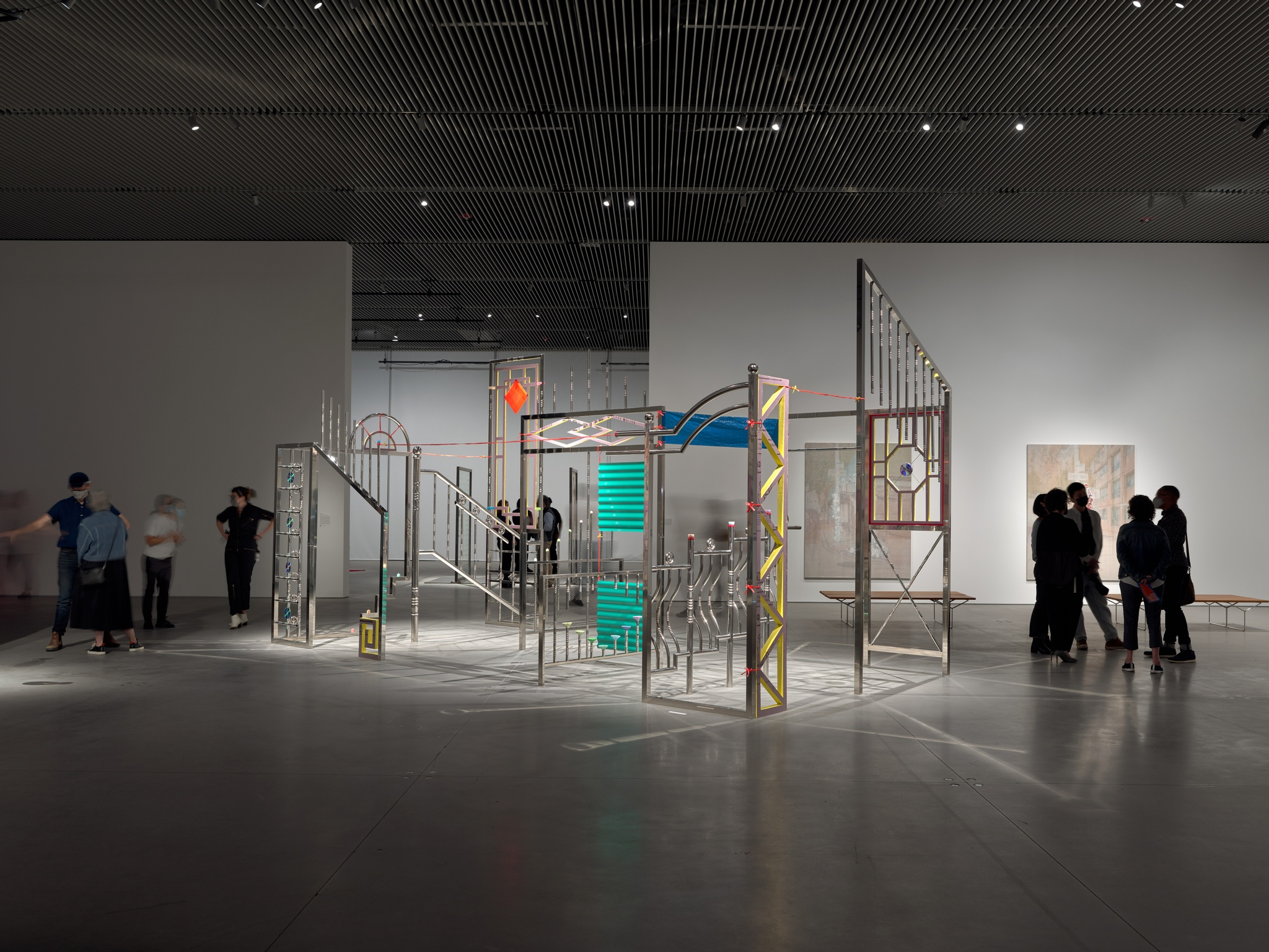In a sparse gallery, large stainless steel rods are tack welded to resemble staircases, doorways, and windows, complete with architectural decorations. The majority of the sculpture is silver, though some of the decorative motifs are yellow, pink, orange, purple, or blue. About a dozen gallery-goers stand next to and behind the installation.