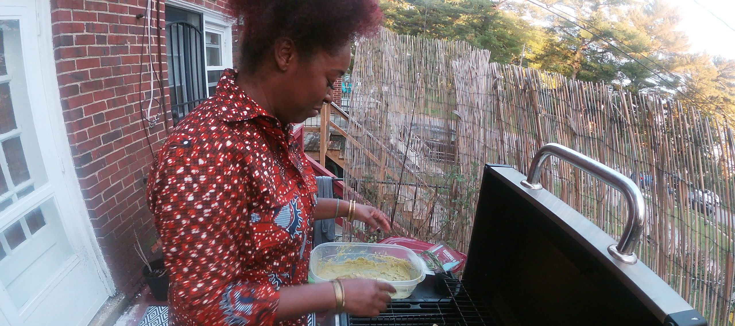 A dark-skinned woman stands on an outdoor balcony, grilling four whole fish on a gas grill. She holds a Tupperware of marinade. The photo is taken with a GoPro, creating a fish eye angle of the scene.