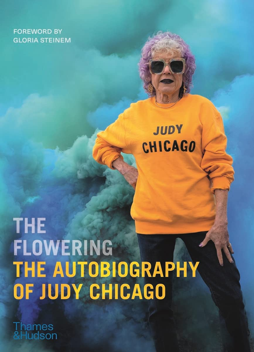 """A book cover features bright blue smoke plumes. A light-skinned older woman with purple, curly hair stands with one hand on her hip. She wears a golden-yellow sweatshirt that says """"JUDY CHICAGO"""" in black letters. Atop the book cover, """"The Flowering: The Autobiography of Judy Chicago"""" is written."""