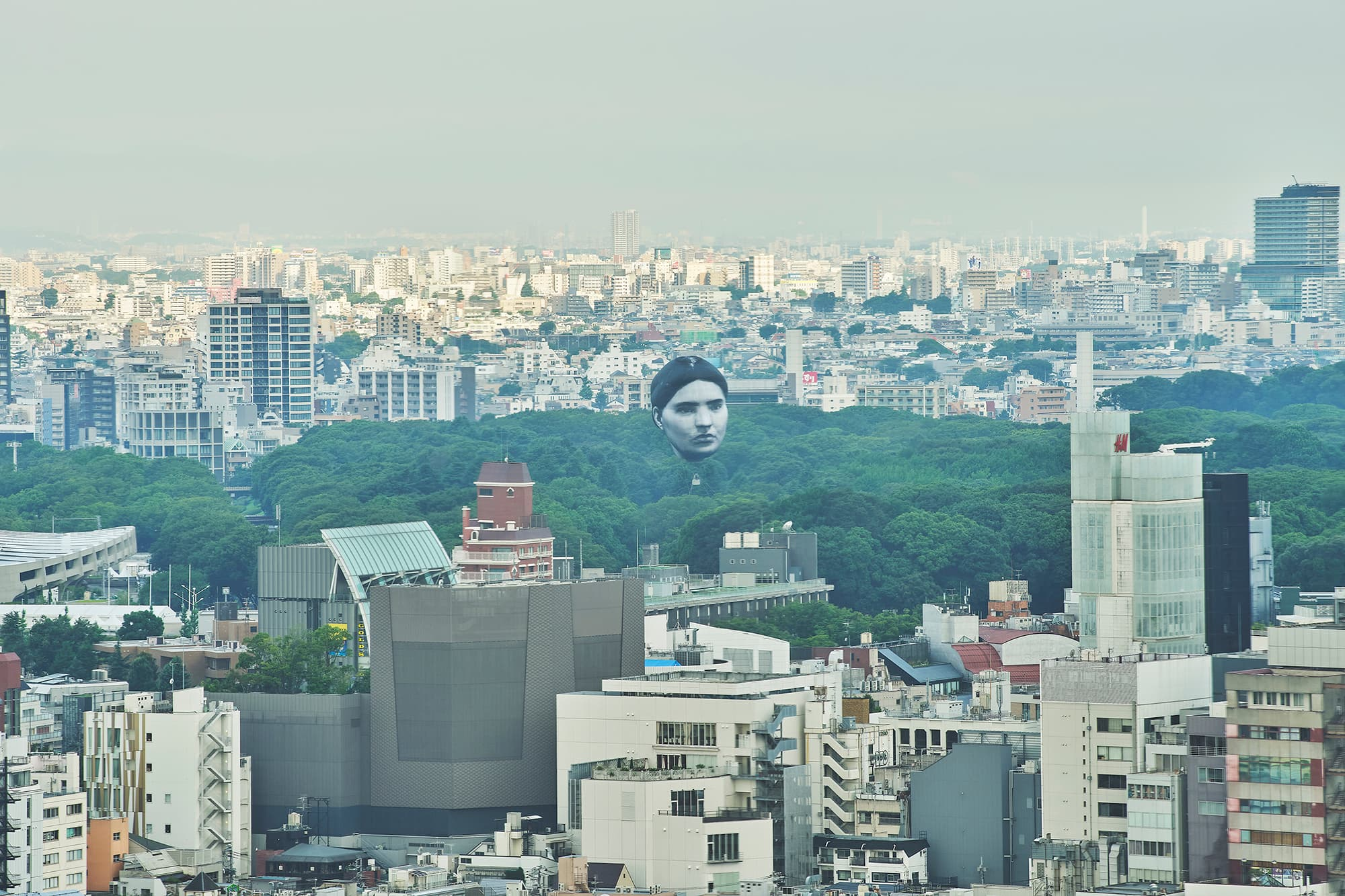 A photo of the Tokyo skyline on a hazy day. In the mid-ground, a sea of green treetops divides the cityscape. Above the trees floats a large balloon face with a black-and-white portrait of an anonymous person. The subject has dark hair parted in the middle, dark eyebrows, and a serious expression.