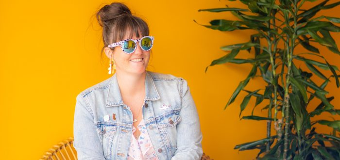 A light-skinned woman sits in a circular rattan chair in front of a bright yellow wall. She wears sunglasses, a jean jacket, a light patterned dress that hits above the knee, and blue sneakers. She smiles off into the distance. Next to her is a tall tropical plant in a terra cotta pot.