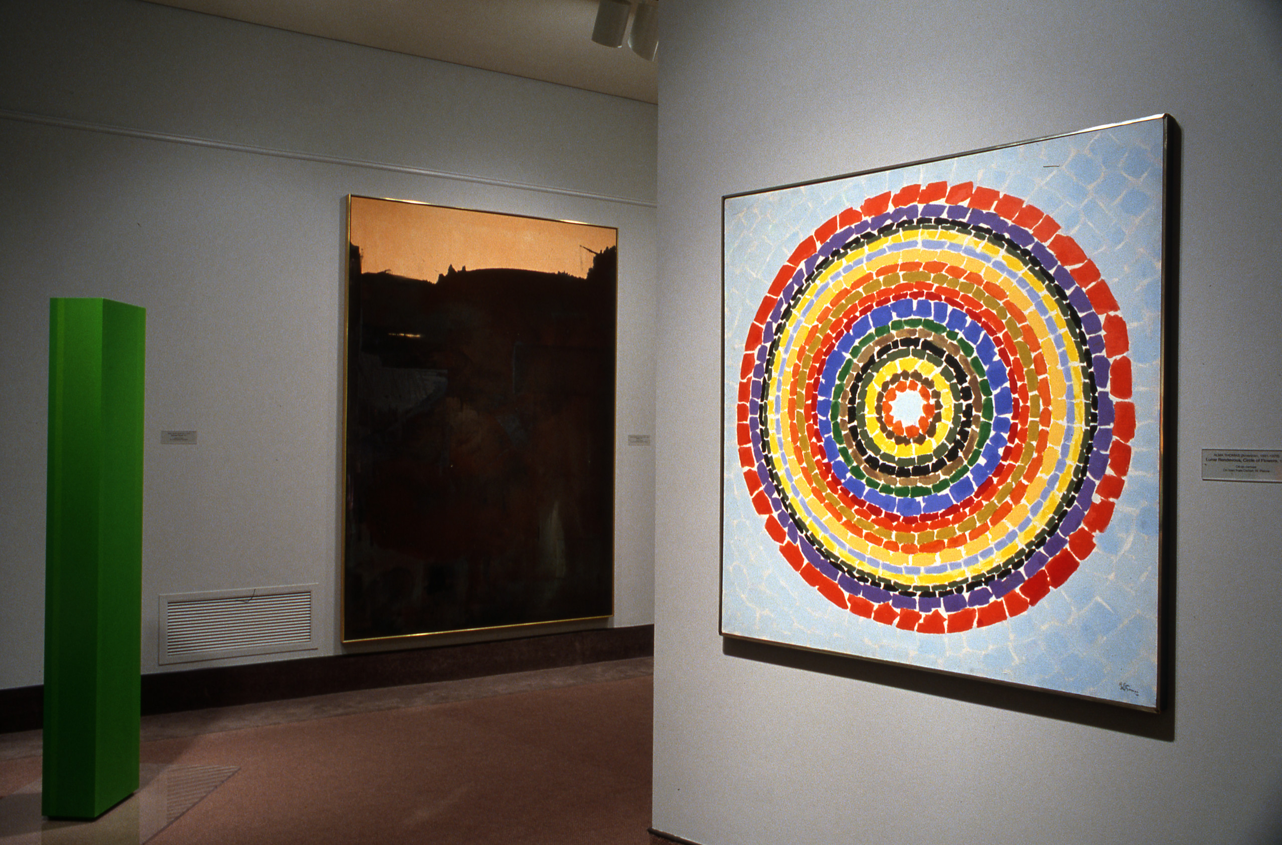 Gallery view of three artworks: a tall green column on the left, a multicolored painting of many concentric circles on the right, and a large black-and-white painting in the background between the two.