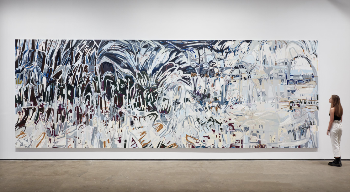 In a white-walled gallery, a light-skinned woman with light brown hair dressed in a black tank top, white pants, and black boots stands to the right of a large, horizontal abstract painting. The canvas features gray, silver, light brown, and tan thick lines painted in waves up and down the canvas. As the canvas moves from left to right, the palette grows progressively lighter in color.