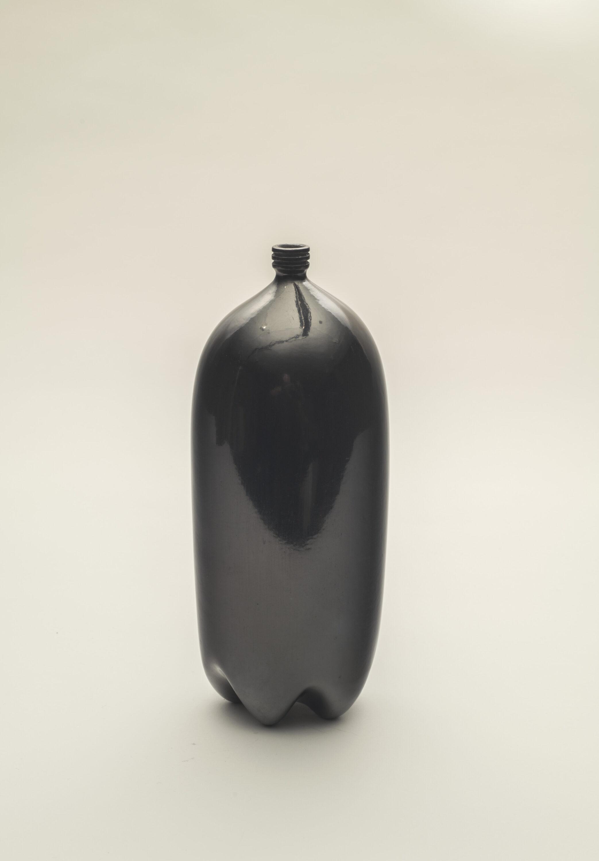 A black clay vessel shaped like a 2 liter soda bottle.