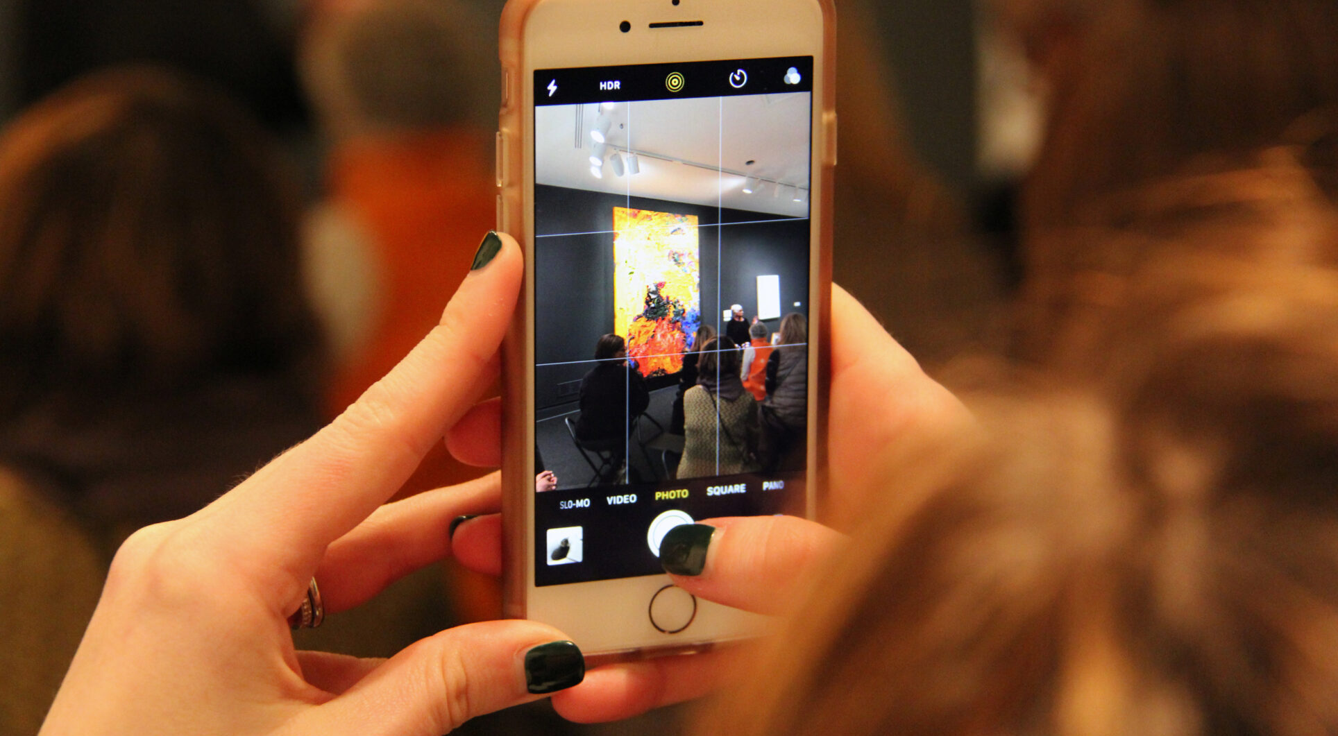 Close-up of hands holding a smartphone recording an artist talk in front of a yellow artwork in the museum.