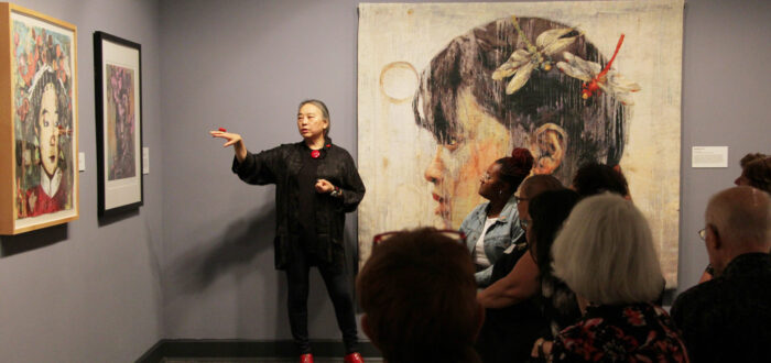 Hung Liu speaks to an audience about her paintings of Chinese women, which hang on the walls around her. Liu is a light-skinned adult woman with gray hair in a low ponytail, dressed in black with red jewelry and shoes. She stands, gesturing with one hand at a painting to her right.