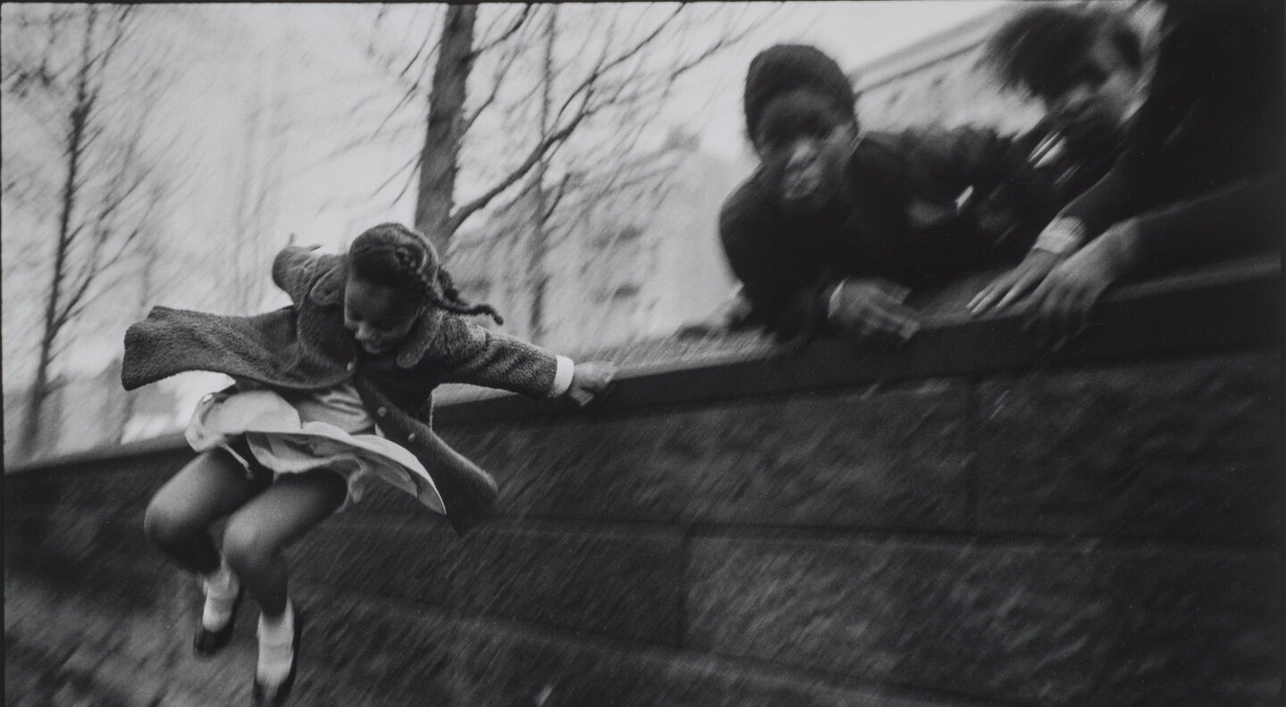 A black and white photograph of a young girl wearing a dress and coat jumping over a brick wall. Three other figures lean over the wall in the upper right corner of the composition. The jumping girl is the only figure who is in focus.