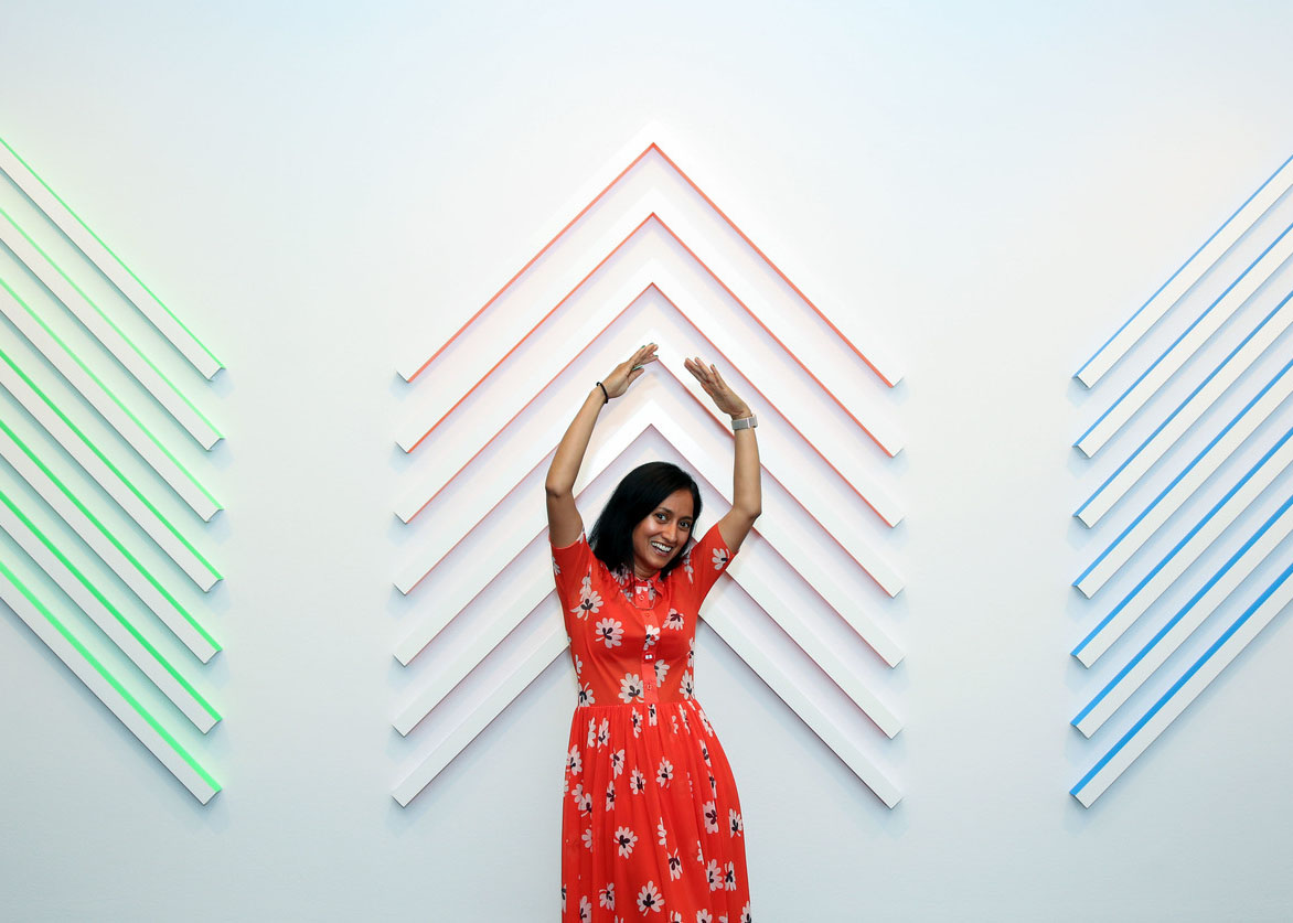 A photograph of a medium-skinned woman with a smile on her face, wearing a red dress with white and black flowers. She stands in front of a geometric wall sculpture with her hands stretched above her head.