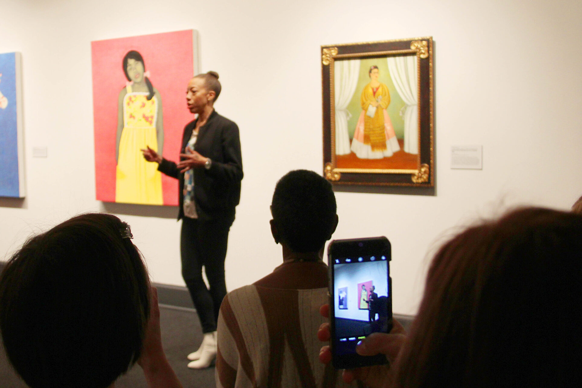 Smartphone filming of a darker skinned woman artist talking in front of her pink and yellow artwork in the museum gallery.