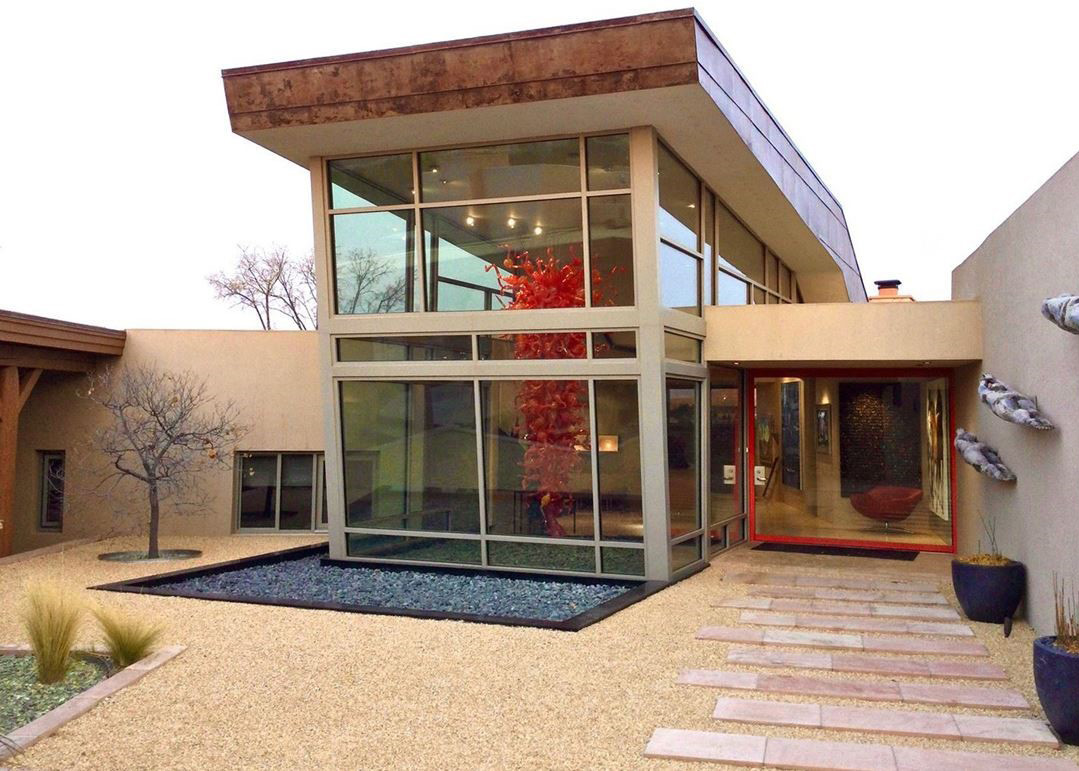 A photograph of a modern style house with a two-story window at the entrance. There are three metal sculptures along the outside wall and a large sculpture hanging from the ceiling inside made of many pieces of curved blown glass.