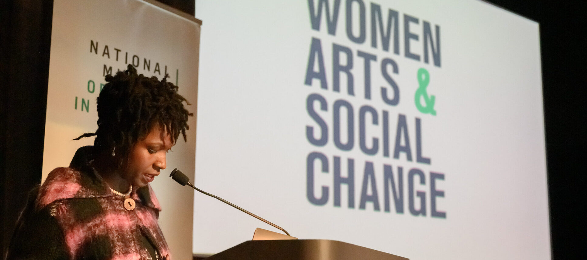 A dark-skinned adult woman stands at a podium at the National Museum of Women in the Arts to speak. She has short dreadlocks, jewelry, and a jacket with a large purple and black plaid print on it. Behind her is a screen with the words 'Women, Arts, & Social Change.'