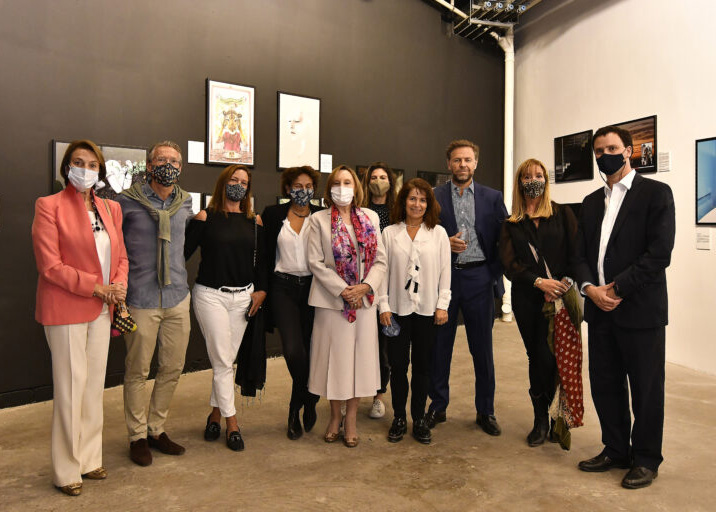 A group of 10 light-skinned men and women stand in front of a wall of artwork. The figures are dressed in smart casual attire and are wearing face masks.