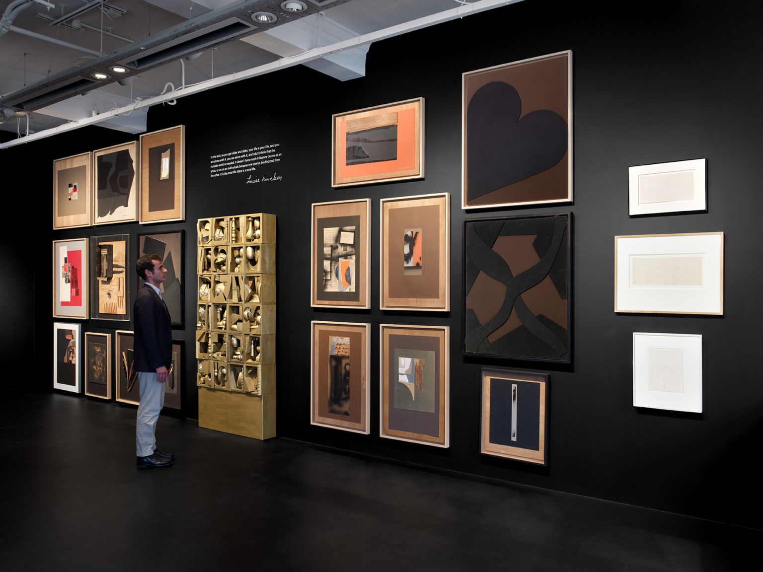 In a gallery with a black floor and walls, a light-skinned, brown-haired man wearing a blazer stands before a wall showcasing 22 of Louise Nevelson's artworks. In the center of the wall stands s sculpture that resembles a bookshelf of knickknacks. A quote by Nevelson is written on the wall space above the bookshelf. Hanging on the walls flanking the bookshelf are several abstract collages and works on paper.