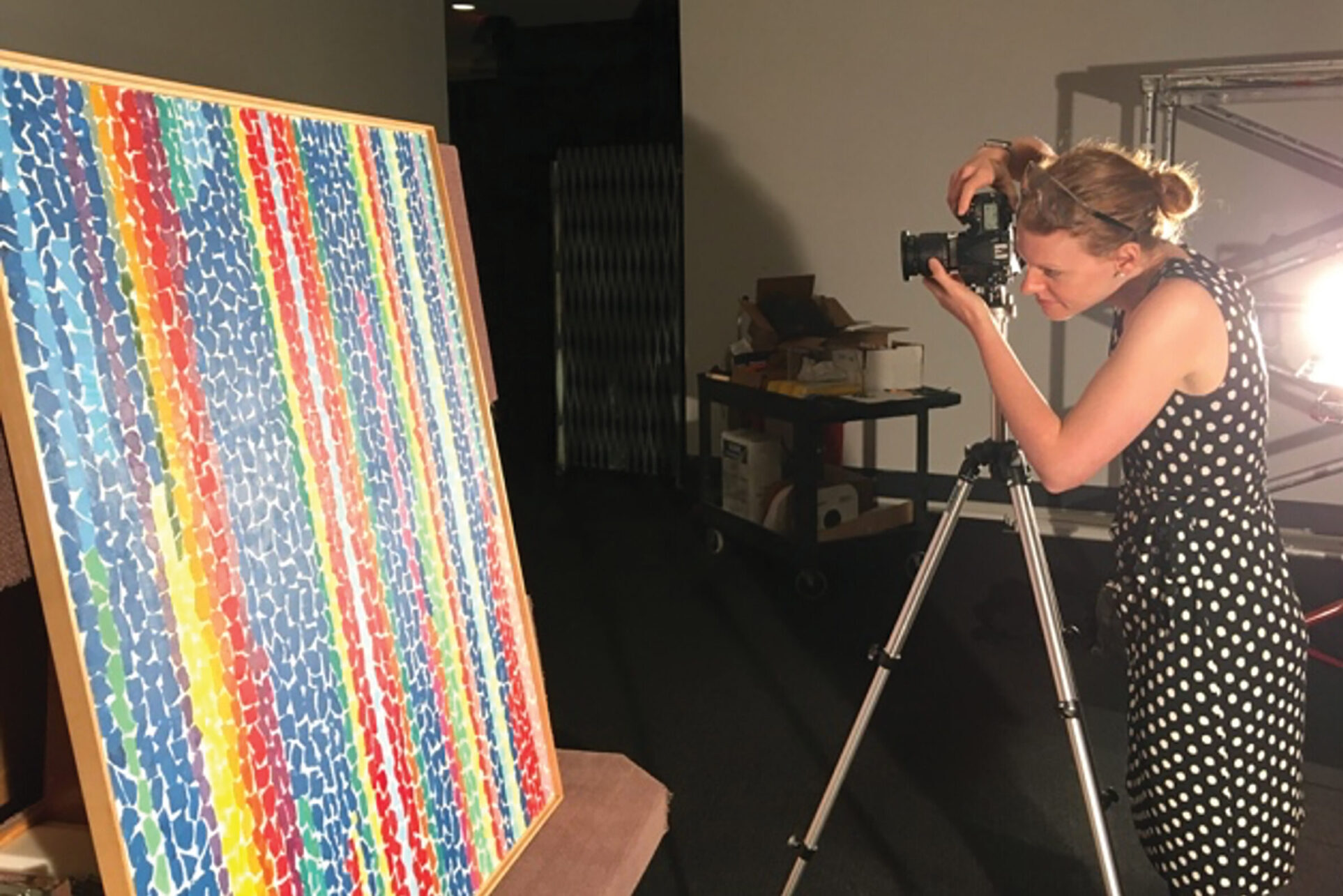 Woman taking a photograph of a colorful striped painting using a camera mounted on a tripod.