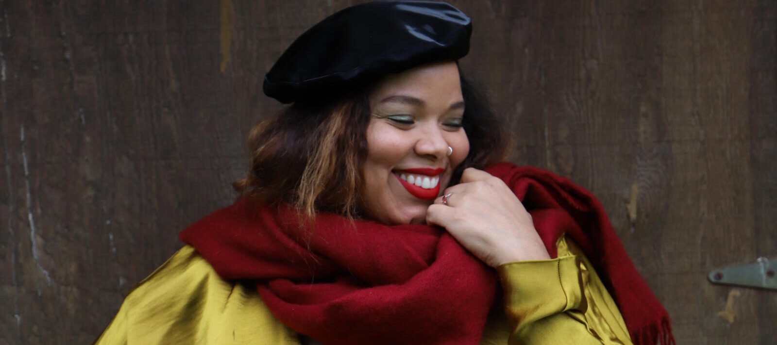 A medium-skinned woman stands in front of an industrial wall wearing a gold silk long sleeve dress with a deep V-neck, a black velour beret, and a cranberry red scarf wrapped loosely aroud her neck. With her right hand on her hip and her left brought up to the scarf, she smiles brightly, looking to the side.
