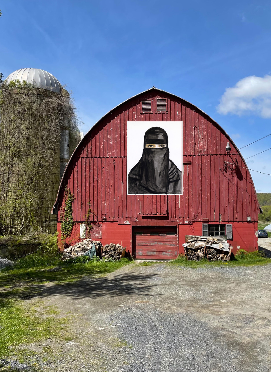 A red wooden barn stands at the end of a gravel lot, with a vine-covered silo behind it. On the barn is a large portrait photograph of a woman wearing a black burqa, only her eyes are revealed. The sky is bright blue and nearly cloudless.
