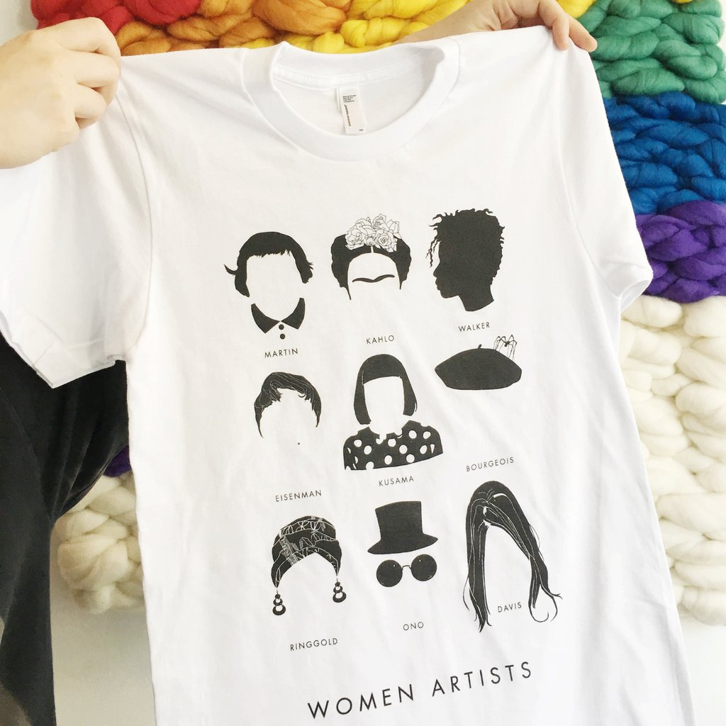 """Two pale hands emerge from the left and hold up a white T-shirt featuring a grid of nine minamalist illustrations of the faces of famous women artists including Frida Kahlo, Kara Walker, Yayoi Kusama, Yoko Ono and more. At the bottom of the grid """"Women Artists"""" is written in clean black type."""