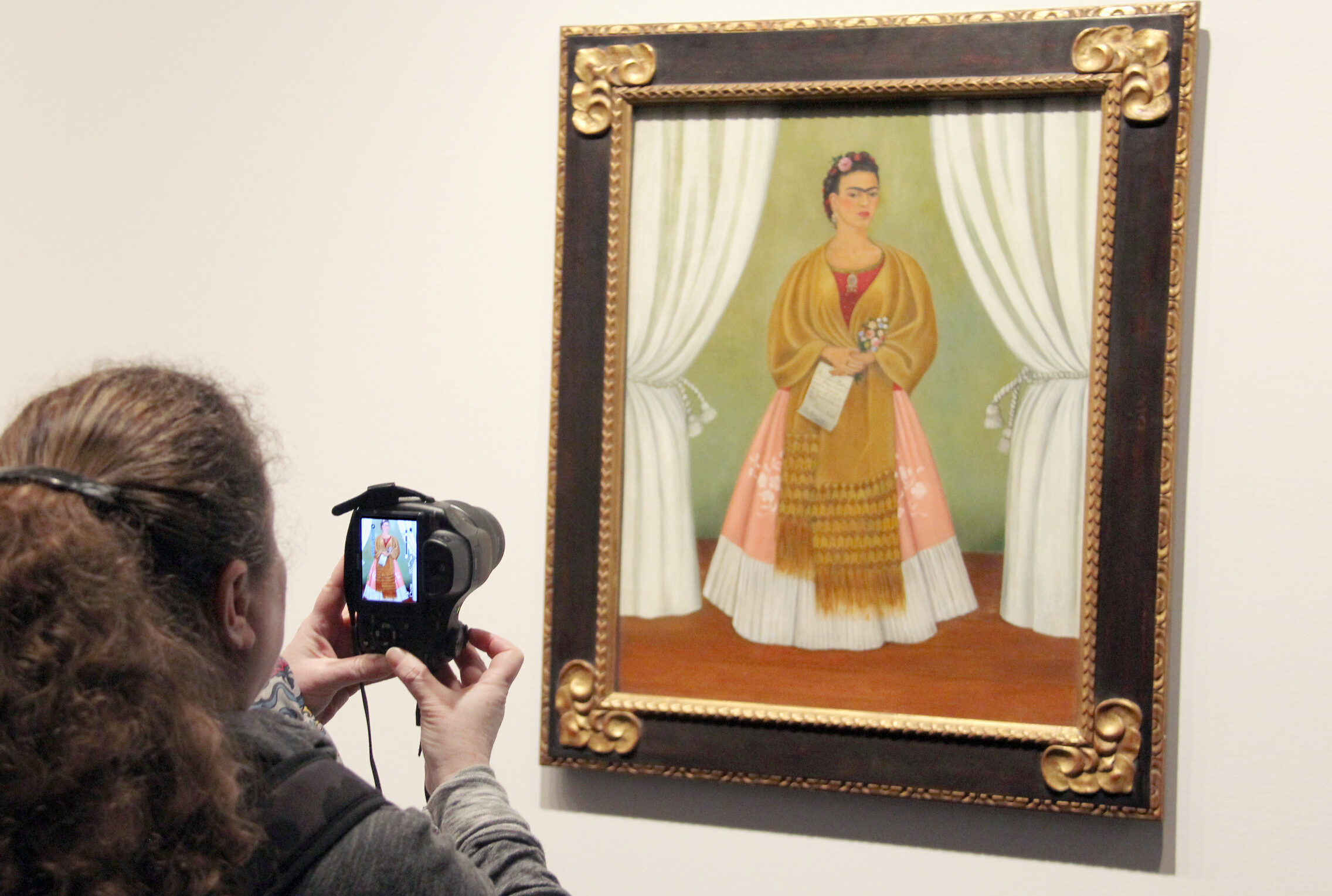View from behind a light-skinned woman with long brown hair taking a photo of a painting of a medium-skinned woman in a dress in the museum galleries.