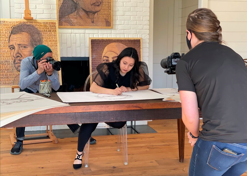 A light-skinned woman with long dark brown hair sits at a wooden table drawing a large face in pencil. A light skinned man with a camera stands behind her and a light skinned woman with a camera stands in front of her. Both figures are photographing her. Behind the artist are three of her finished portraits.