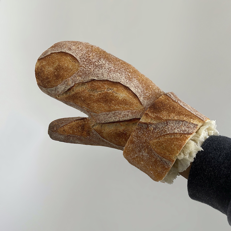 A photograph of a hand wearing a mitten. The mitten is made out of a loaf of rustic bread.