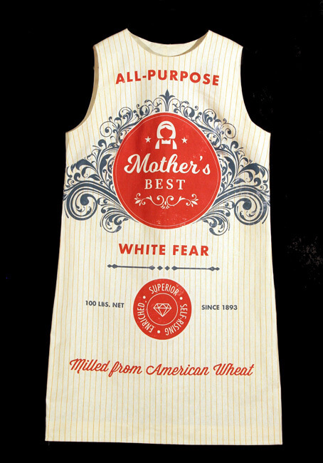 """A sleeveless white dress, with a simple rectangular silhouette, features red and blue flour sack imagery printed atop it. It reads, """"All-Purpose,"""" """"Mother's Best,"""" """"White Fear,"""" and """"Made from American Wheat."""""""