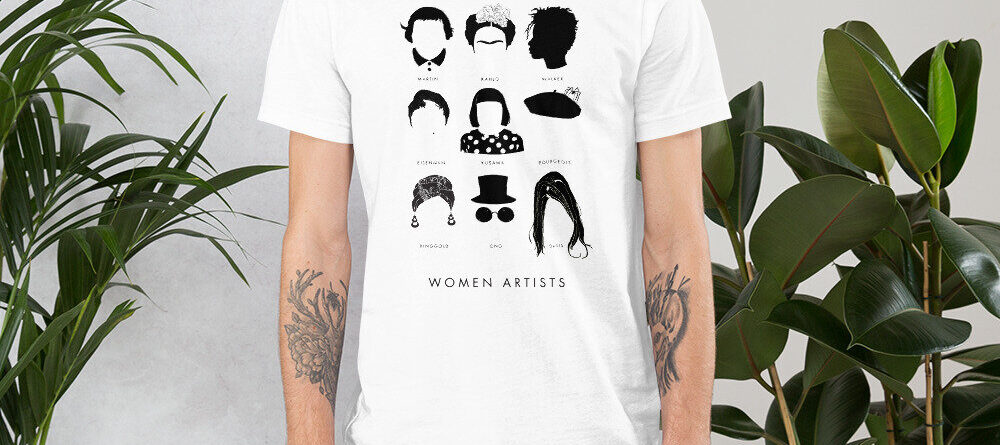 A light-skinned adult wears a white t-shirt that has a three by three array of nine illustrations featuring the iconic hair and accessories of famous women artists. Underneath each illustration is the artist's name, and underneath the group are the words 'women artists.'