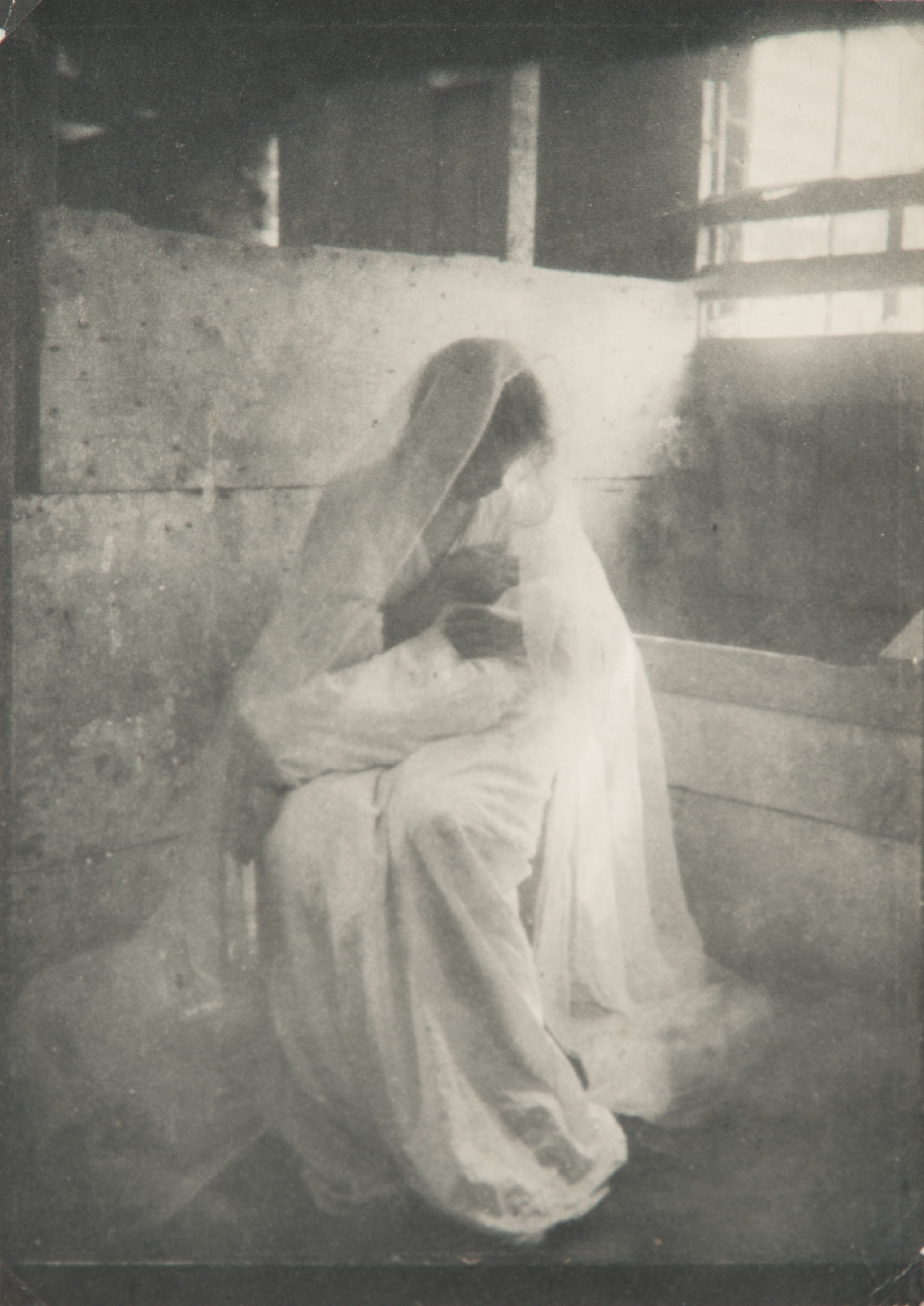 Ethereal black-and-white photograph of a women wearing a long white dress and gossamer veil, sitting in a stable, holding a swaddled infant. Dramatically illuminated by a shaft of light streaming in, she gazes down at the child cradled in her arms.