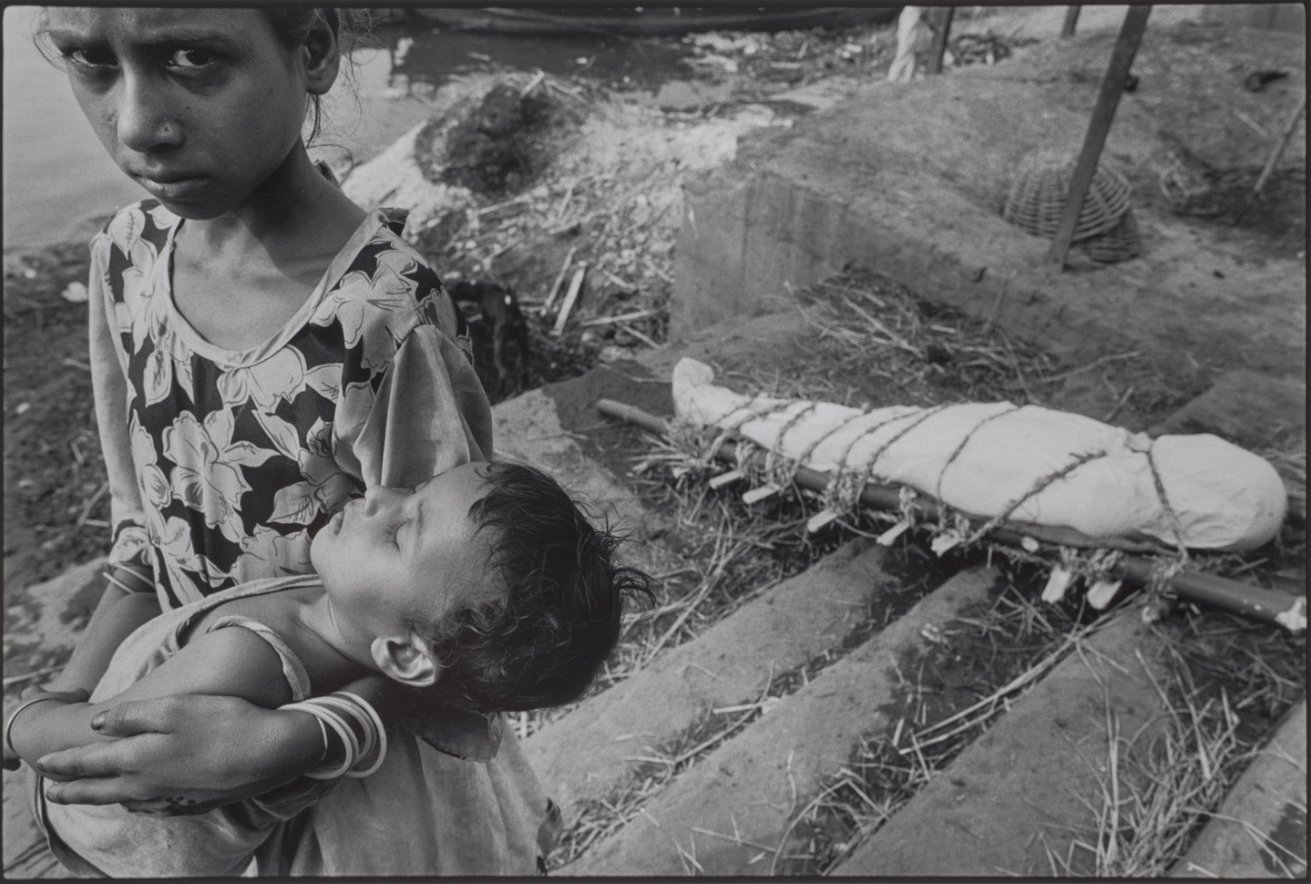A black-and-white photograph of a child with medium skin tone carries a sleeping baby and stares into the camera with a distraught look on her face. In the background, a dead body is wrapped in white cloth and tied to a makeshift stretcher.