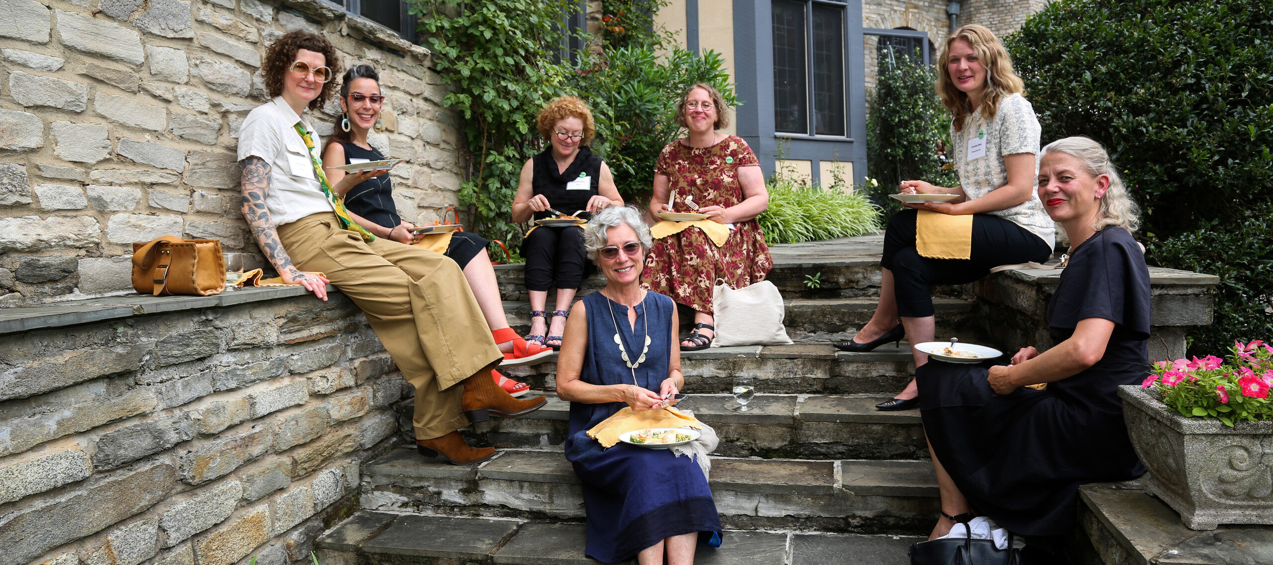 A photograph of seven light skinned women seated on stone steps eating lunch with plates and napkins in their laps. The women are looking at the camera and smiling. There is a Tudor style home in the background.
