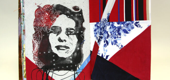A book made from colorful print fabrics collaged and stitched together is laid flat and open to a spread that features an stencil cut image of a woman's face overlaid with an intricate flower positioned on her hair.