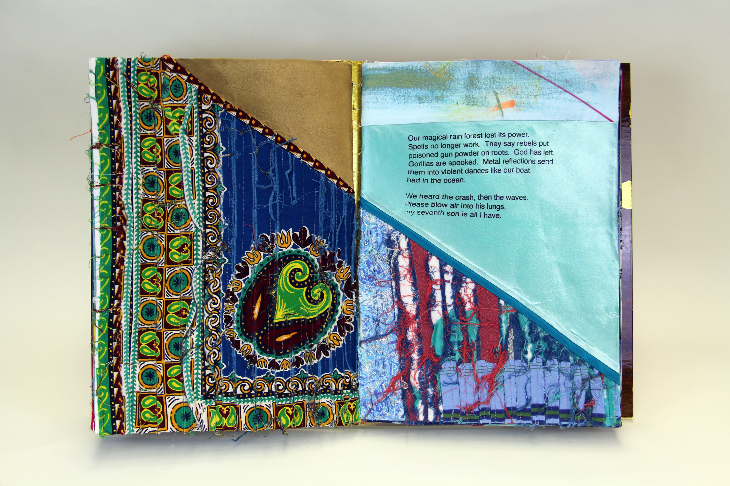 A book made from colorful print fabrics collaged and stitched together is laid flat and open to a spread that features a vibrant African prints and a short poem.