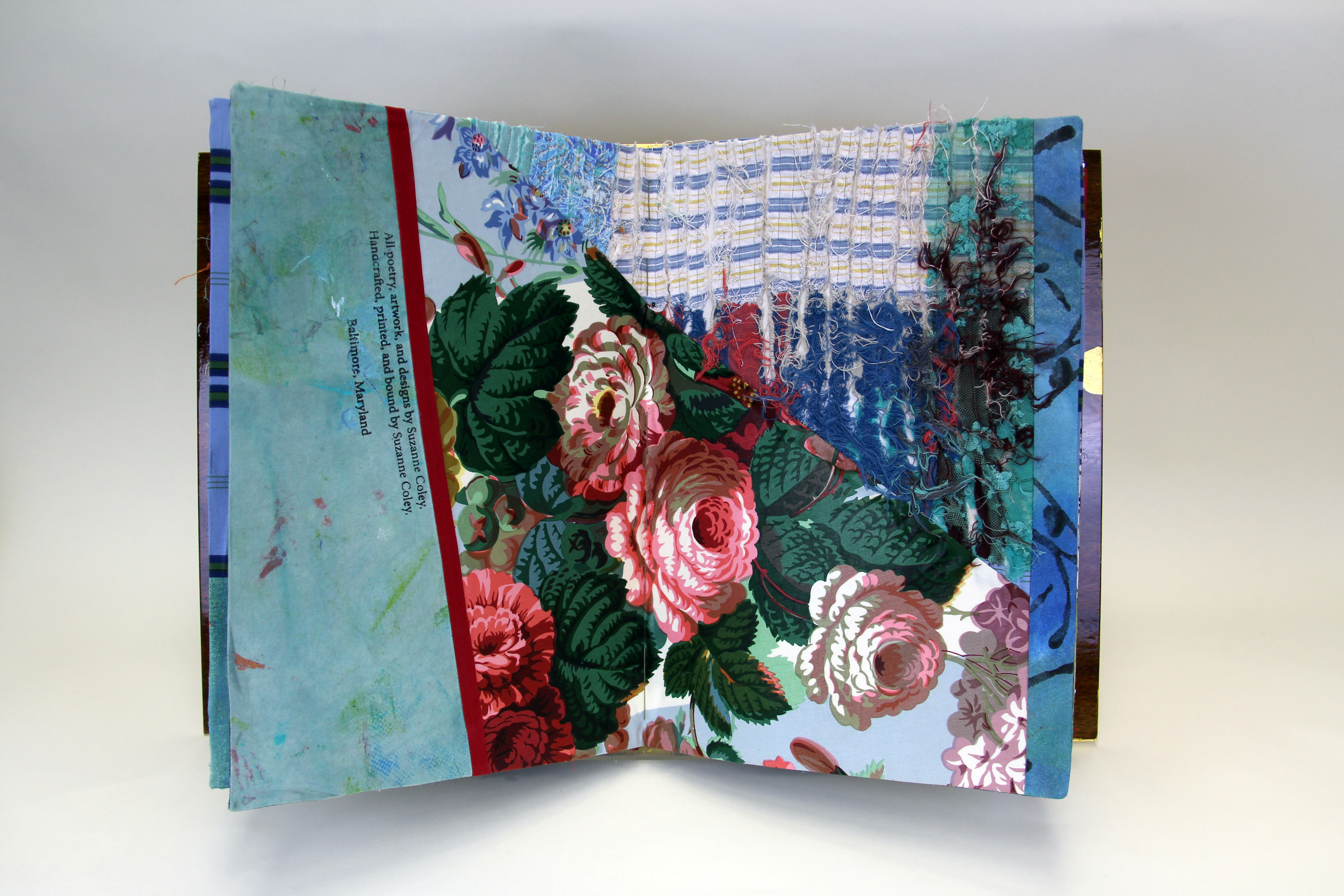 A book made from colorful print fabrics collaged and stitched together is laid flat and open to a spread that features a vibrant floral print.