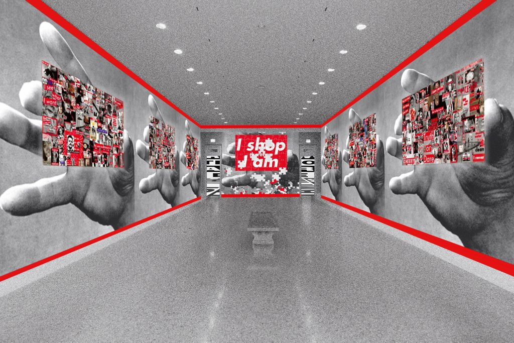"""A rendering of a museum entryway features shiny, stark white floors and a low bench in the middle of the passage. On all of the walls, large black-and-white photos of a hand, mid-reach, are overlaid with busy collages of unknown photos that are marked with red. At the very back wall the phrase """"I shop therefore I am"""" is prominently displayed in white text on a red square background atop one of the hands."""