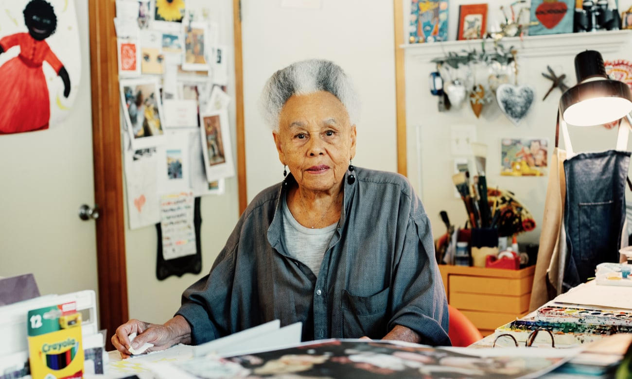 An older light-skinned African American woman sits at a table in an art studio, filled with papers hanging on the wall, craft materials, and cards and personal treasures. She stares at the camera, unsmiling but pleasant, and her white and grey hair is styled in a neat, cropped afro