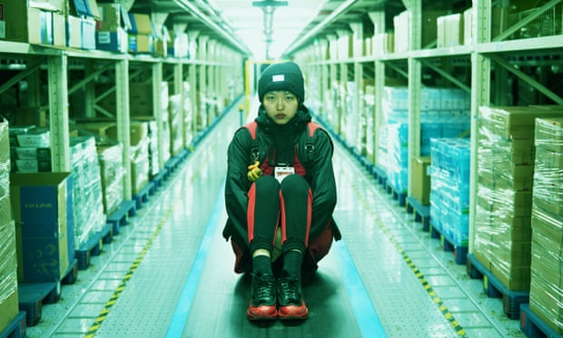 A light-skinned woman of Asian descent wears a black beanie, black jacket, and black leggings and shoes striped with red. She sits in the middle of a long, artificially-lit corridor in a warehouse, her knees bought to her chest and her hands clasped beneath them. She looks at the camera unsmiling, with an uneasy but defiant expression on her face. On either side of her, plastic-wrapped boxes on shipping palates are lined and stacked atop industrial shelving.