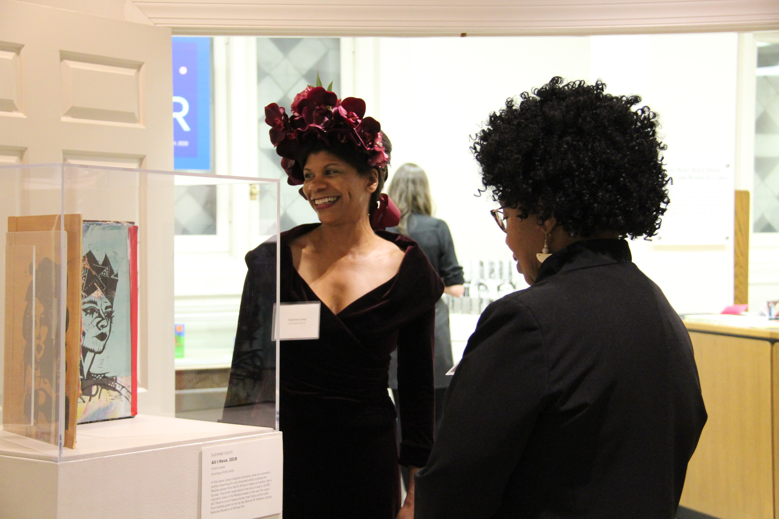 A dark-skinned woman wearing a maroon velvet floral headpiece and a velvet dress of the same color stands in front of an exhibition case smiling and looking toward the artwork in the case. Another dark-skinned woman stands with her back to the camera viewing the artwork.