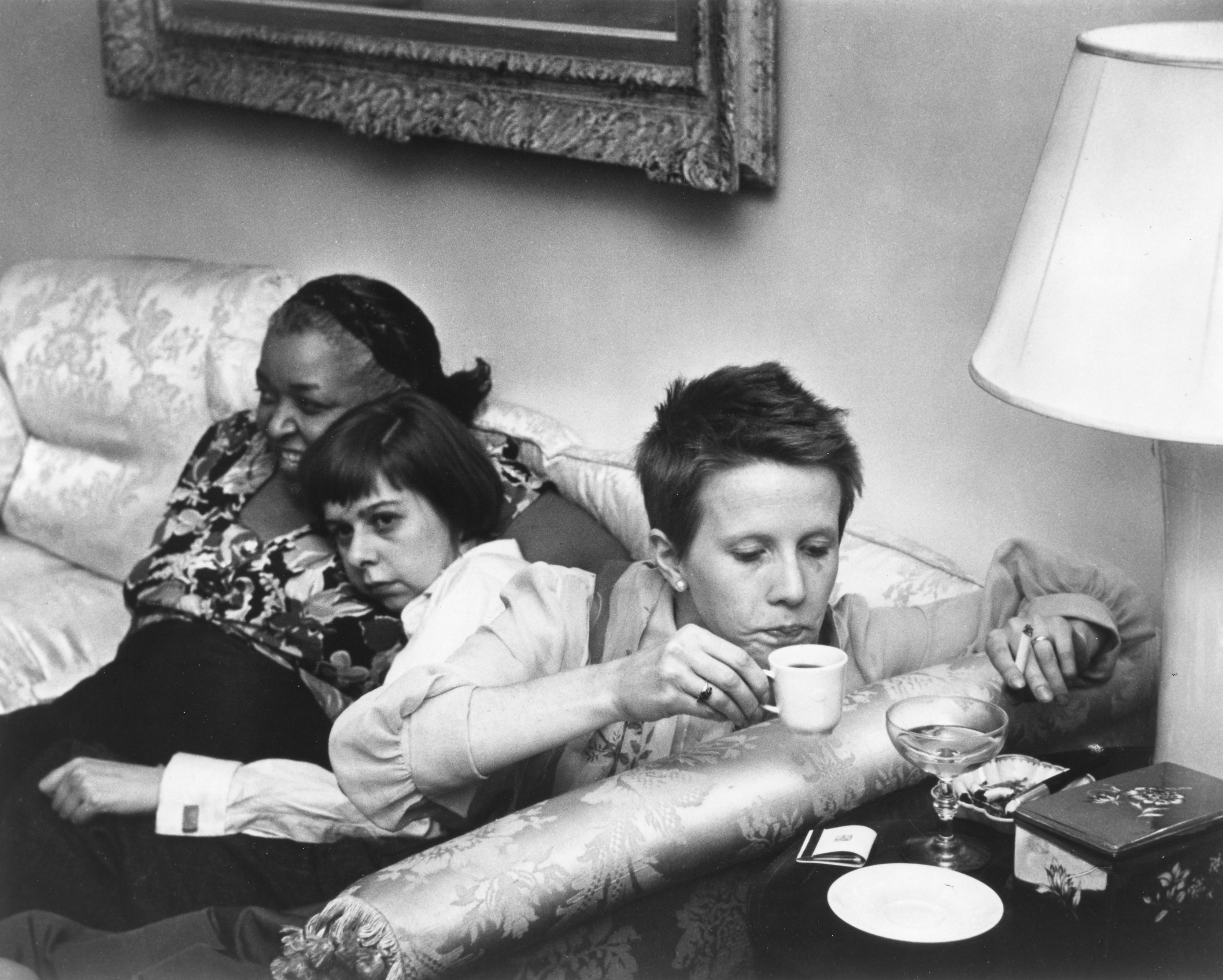 Three women sit on a couch, facing in different directions. At left, a dark-skinned woman faces out, to the left of the camera, and smiles; a light-skinned woman with bobbed dark hair leans on the first woman and gazes down. At right, a light-skinned woman with short hair leans over to lift a cup of tea and cigarette from a side table.