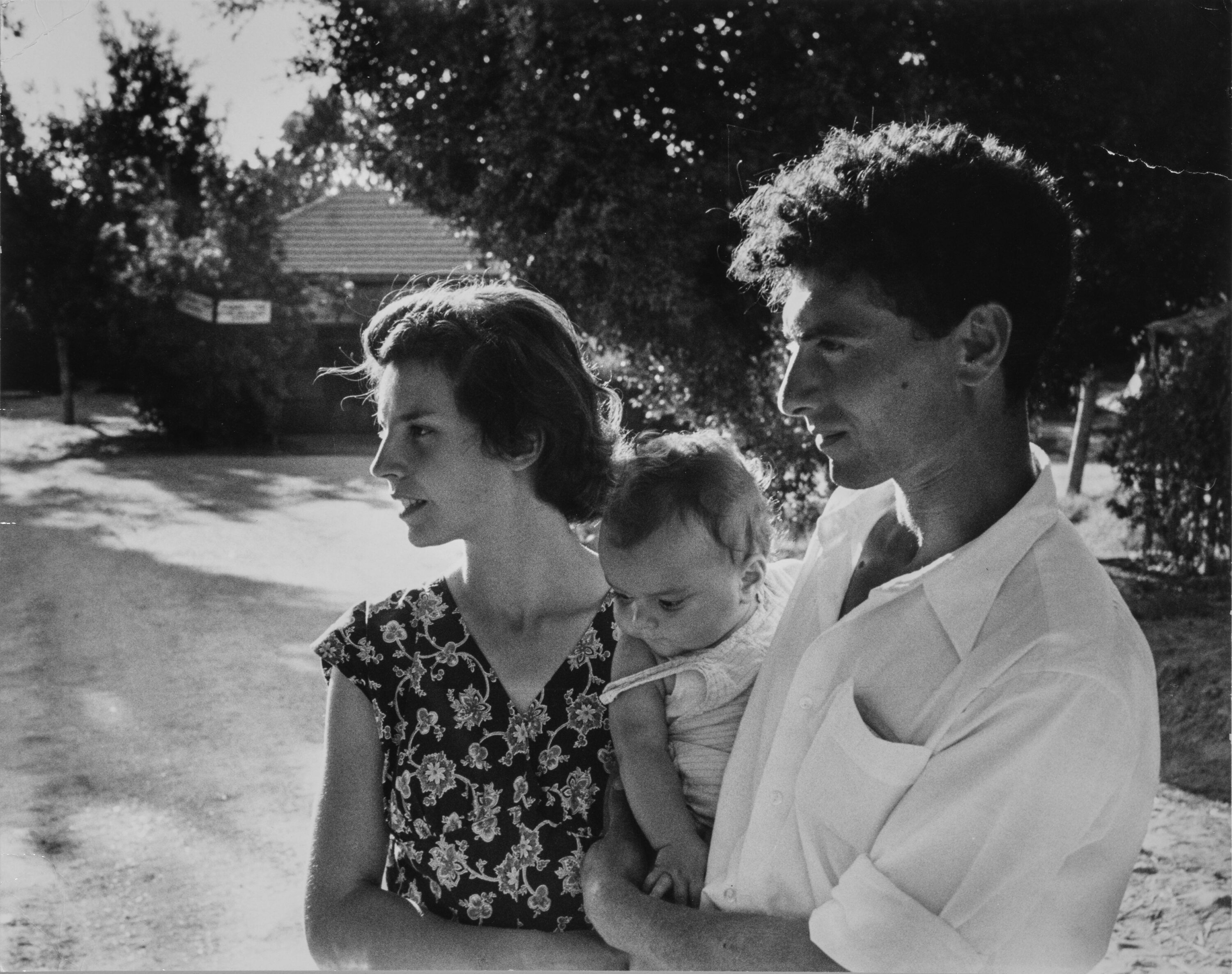 A man stands next to a woman holding a baby on his hip between the two of them; all the figures have light skin tone and brown hair. The adults are seen in profile looking to the left at something out of the frame. They are in a sunny outdoor setting in front of trees and a structure in the distance.