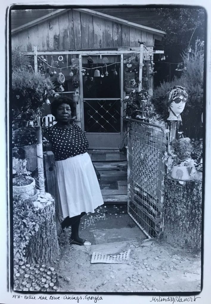 A black-and-white photo features a dark-skinned woman wearing a light skirt and polka-dotted blouse standing at the gate entrance to a small wooden house. She leans on a wooden pillar and stares confidently at the camera.